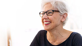 Photo of a lady with white hair and glasses grinning.