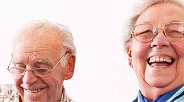 A photo of an elderly couple laughing.
