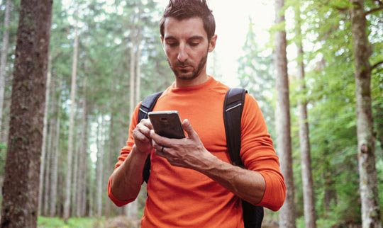 Man hiking through a forest and using his smartphone
