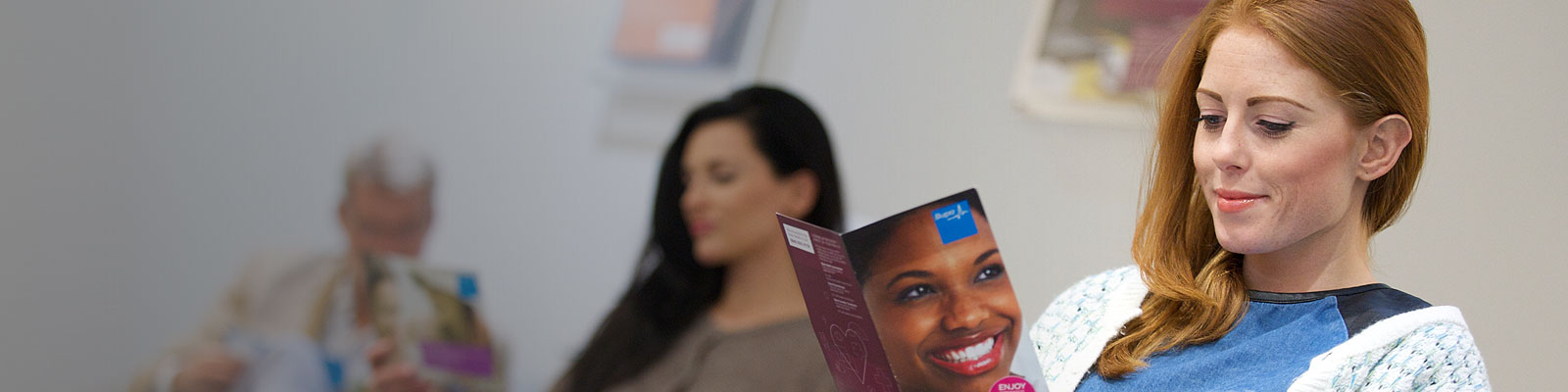 Woman in dentist waiting room, reading booklet
