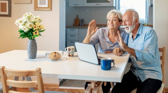 Senior couple sat at table waving on video call
