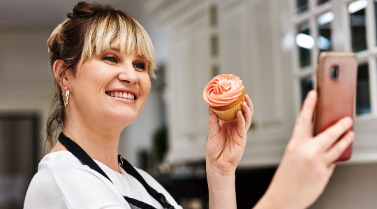 Happy woman taking selfie with cupcake