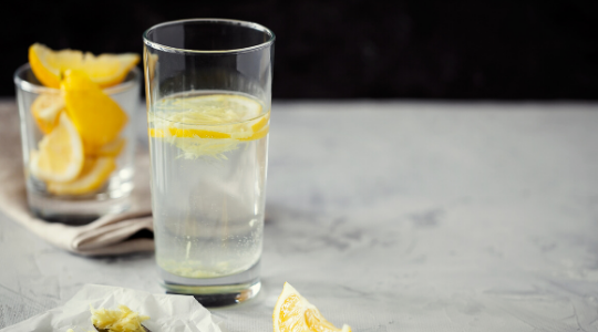 a glass of lemon water surrounded by sliced lemons on a marble work surface