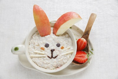 Porridge with a bunny face made using apples and blueberries