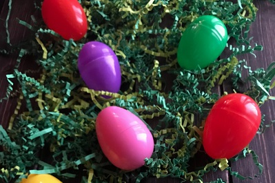coloured plastic eggs on cut-up green paper