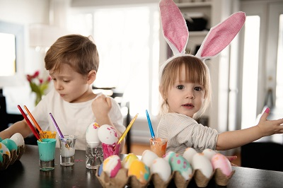 Kids decorating hard-boiled eggs with colourful paints