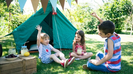Three children smiling and playing outdoors next to tent