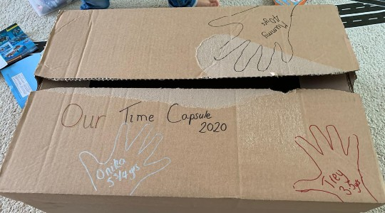 Homemade time capsule using cardboard box with handprints drawn on