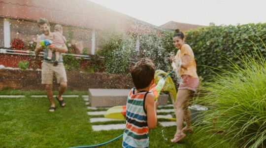 Family having water fight in garden using hosepipe and water pistols