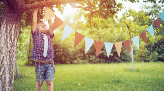 Boy hanging up bunting in the garden