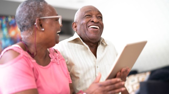 Man and woman laughing with iPad