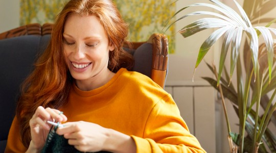Happy young woman knitting at home