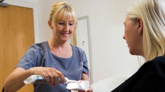 Dentist at Bupa Dental Care offering tooth brushing guidance to patient