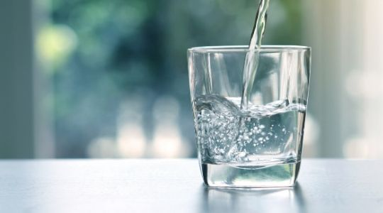 Close up of water being poured into a glass on the kitchen side