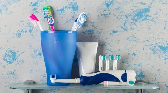 Manual toothbrushes in a pot with electric toothbrush and replacement head laid down on a glass shelf
