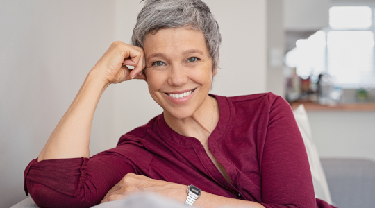 Middle-aged woman with short grey hair showing her perfect smile