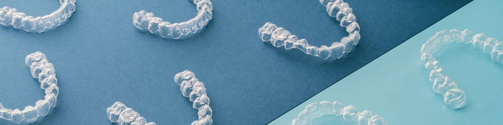 Invisalign aligners laid out on a blue background