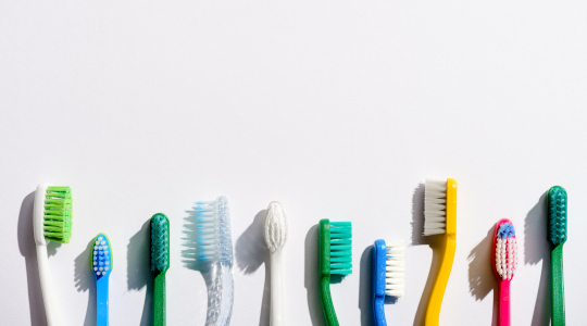 Coloured toothbrushes lined up against plain background
