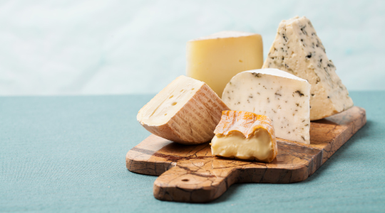 a selection of cheeses on a marble board