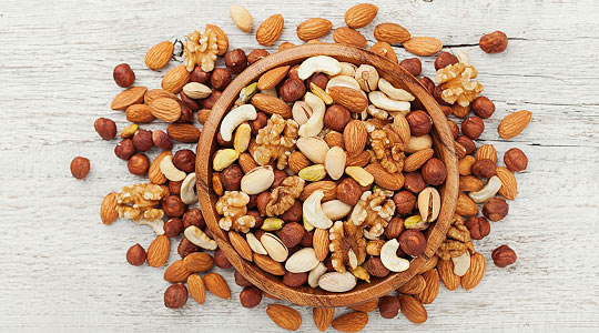 Wooden bowl with filled with walnut, pistachios, almonds, hazelnuts and cashews, on white table top view