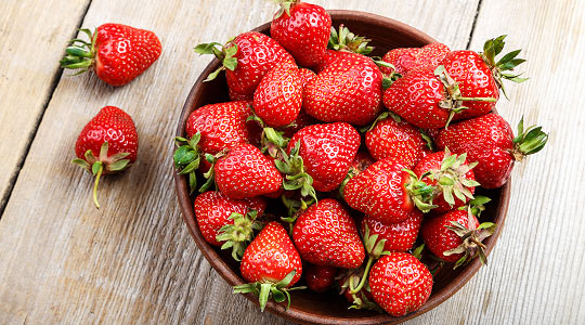 a bowl of ripe strawberries on a wooden table