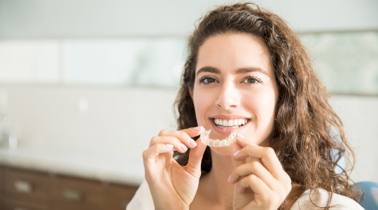 Lady smiling holding orthodontic retainer