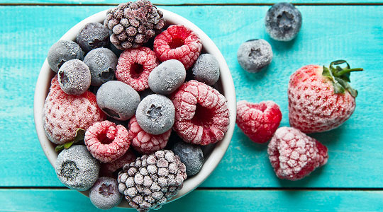 Large bowl of frozen fruit dusted in ice