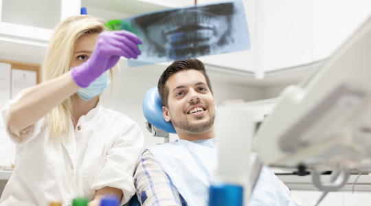 Young man in the dentist's chair, smiling as he is treated for the effects of teeth grinding