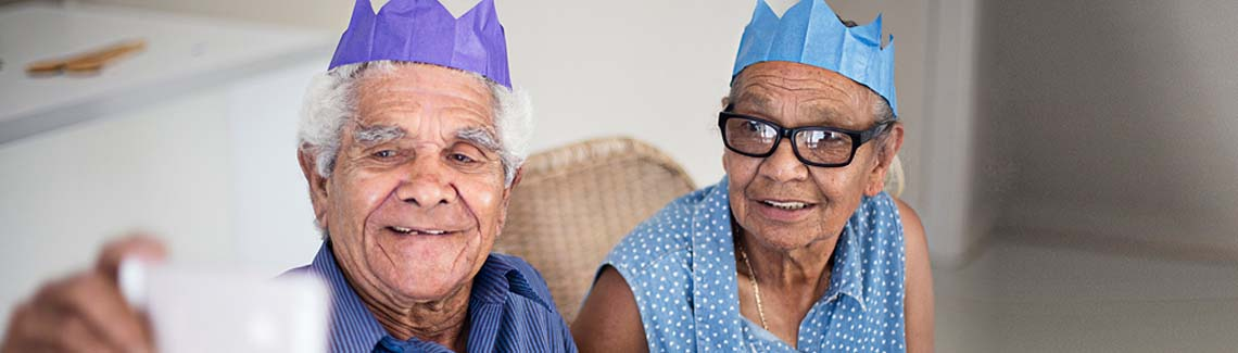 A photo of an elderly couple in Christmas cracker hats taking a selfie photo.