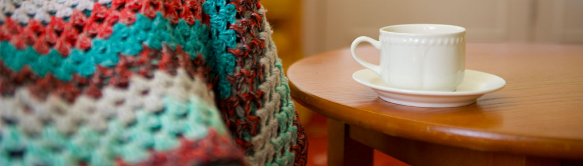 A photo of a hot drink in a mug on a saucer next to a multi-coloured crocheted blanket.