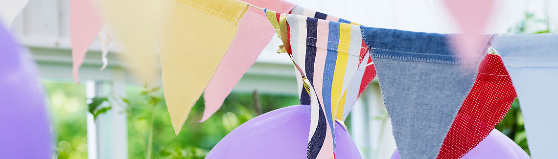A photo of some purple balloons and some multi-coloured bunting.