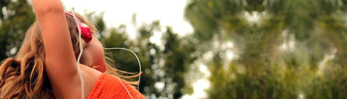 A photo of a young girl in an orange dress wearing headphones and dancing.