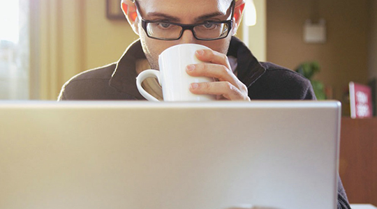 Man looking at a laptop whilst drinking a hot drink