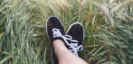 a picture of a pair of feet in some long grass