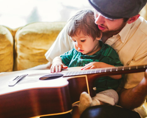 man playing guitar with a child