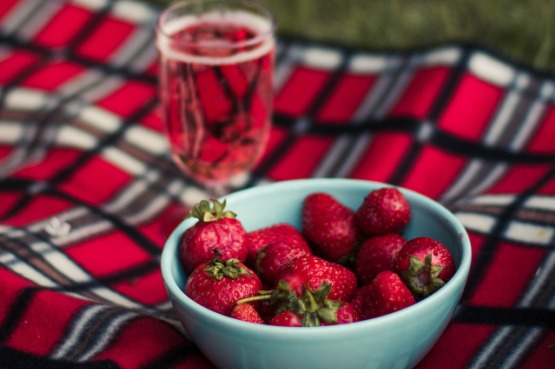 A bowl of strawberries on a picnic blanket