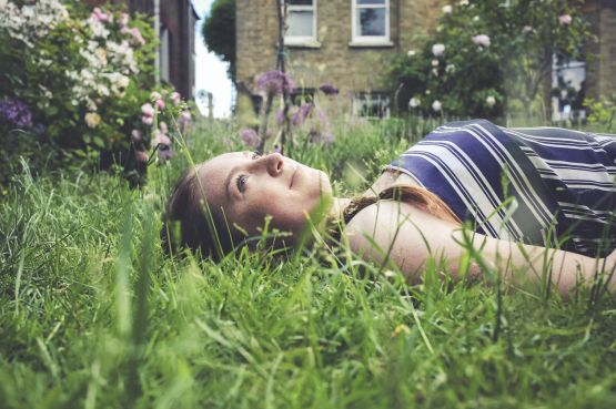 A girl lying down in grass