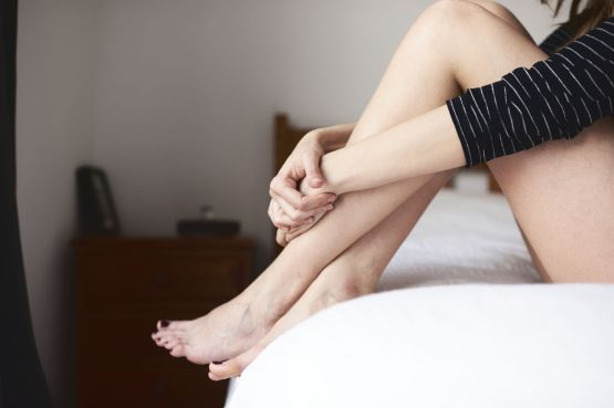 Close-up of young woman embracing her naked legs while sitting on bed
