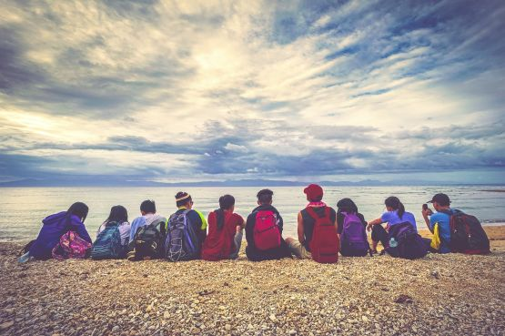 children with backpacks, sitting on a pebbled beach looking into the horizon
