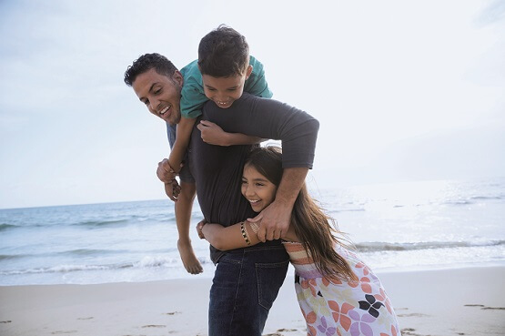 A dad and two kids enjoying themselves on the beach