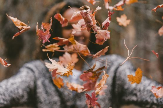 An image of a girl throwing Autumn leaves