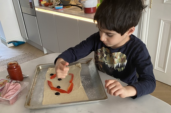 a little boy making pizza at home