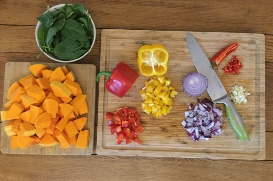 chopped vegetables on a board and a bowl of spinach leaves