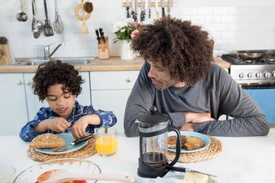 father and son eating breakfast in the kitchen