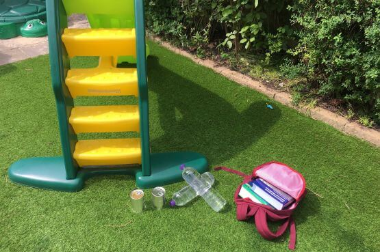 a children's slide, 2 tin cans, 2 water bottles, a bookbag