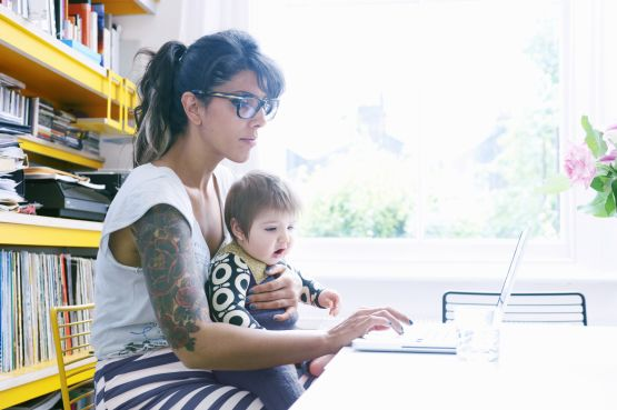lady with a toddler on lap, working at a laptop