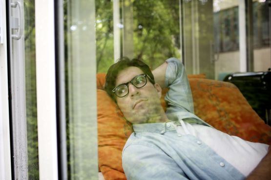 a man lying down, looking out of the window