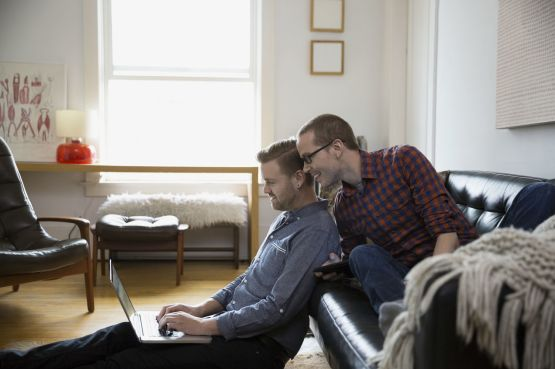 two men at home looking at a laptop