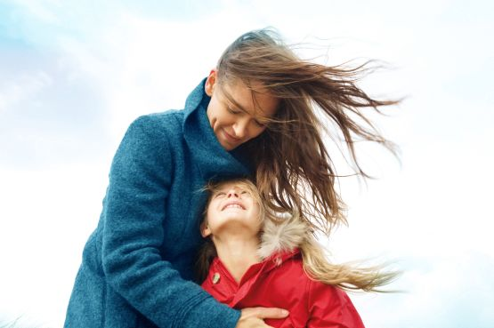 woman holding a girl on a windy day