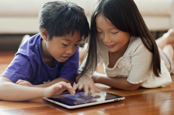 Two children looking at a tablet computer